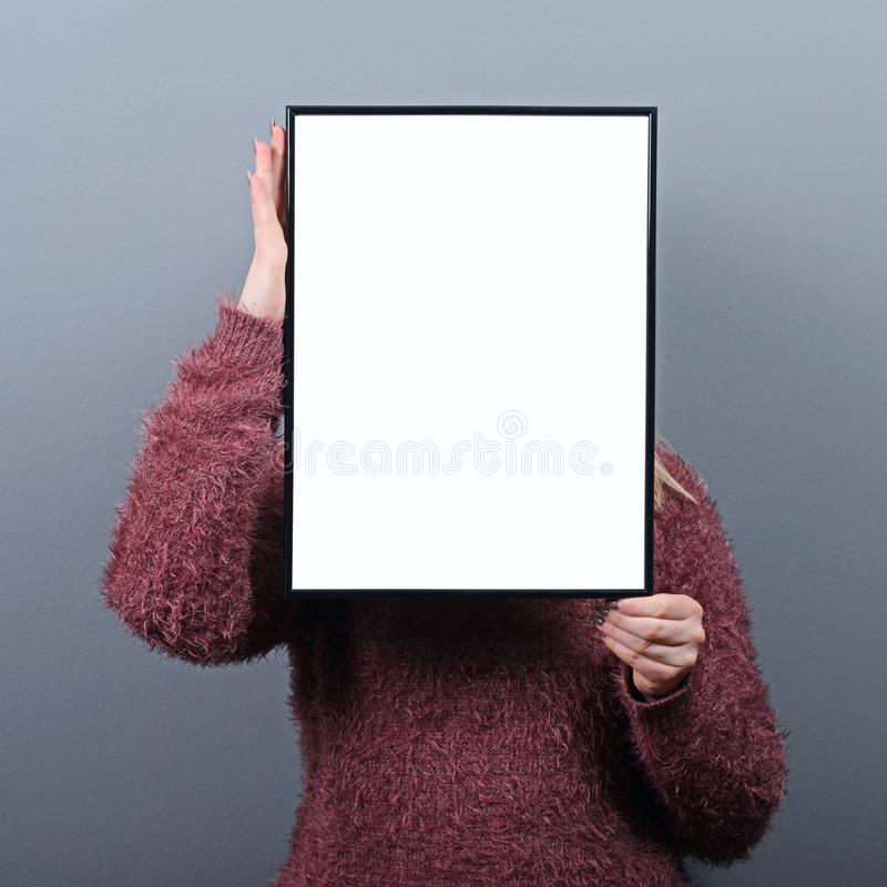 Retrato da mulher que esconde atrás da placa vazia do sinal fotografia de stock