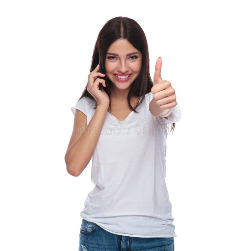 Retrato da mulher que fala no telefone que faz o sinal aprovado imagem de stock royalty free