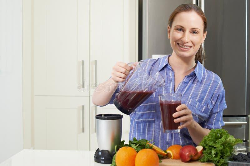 Retrato da mulher que faz Juice Or Smoothie In Kitchen imagens de stock