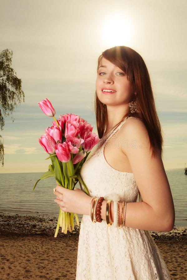 Retrato da mulher que guarda flores cor-de-rosa na praia foto de stock royalty free