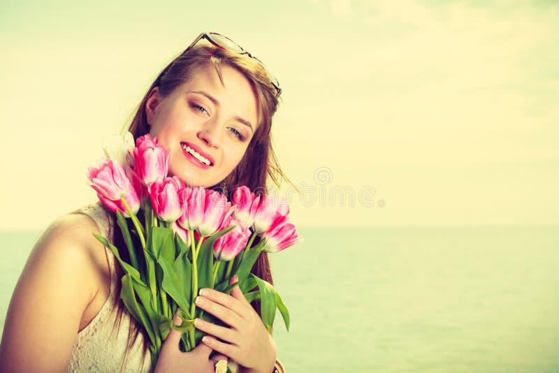 Retrato da mulher que guarda flores na praia imagens de stock royalty free