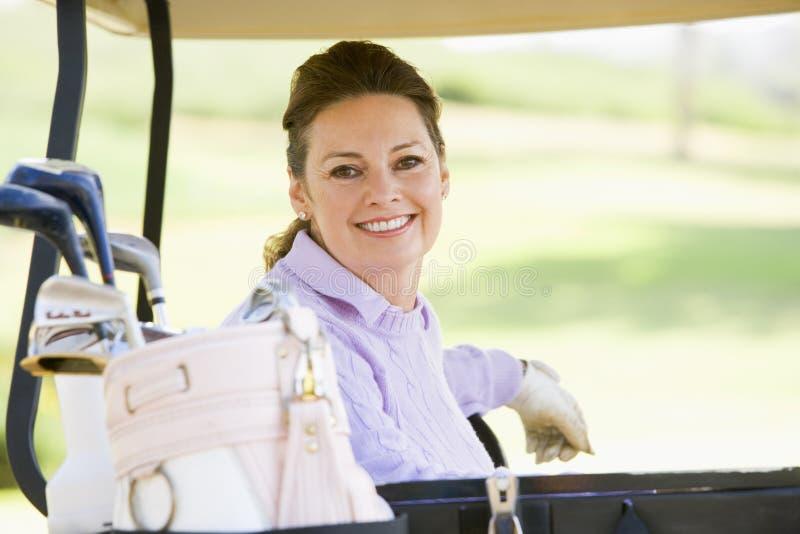 Retrato da mulher que senta-se em um carro de golfe imagens de stock