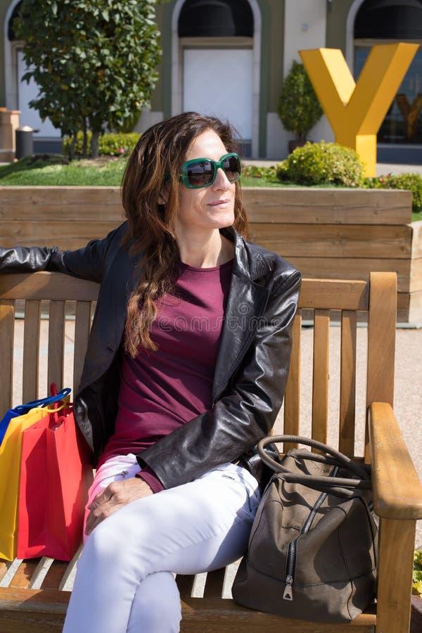 Retrato da mulher que senta-se no banco com sacos de compras e bolsa foto de stock royalty free