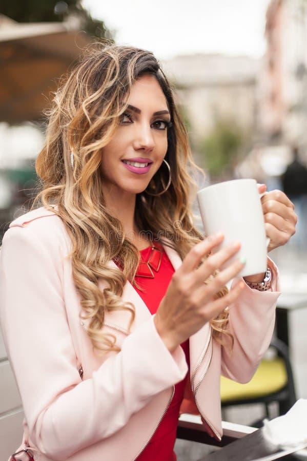Retrato da mulher que senta-se no caf? exterior e no caf? bebendo fotos de stock