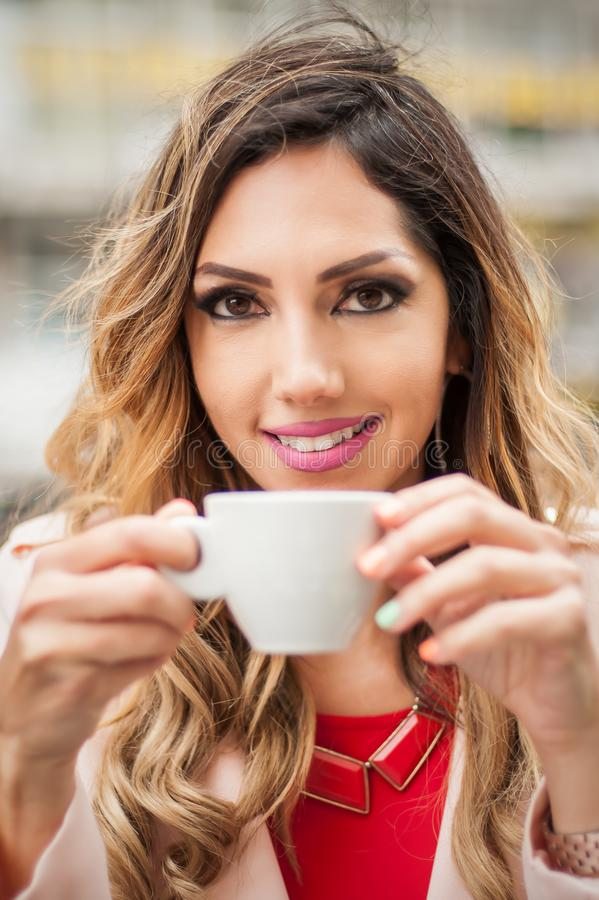 Retrato da mulher que senta-se no caf? exterior e no caf? bebendo imagem de stock royalty free