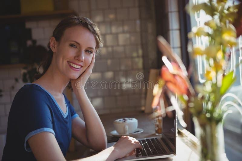 Retrato da mulher que usa o portátil no peitoril da janela fotografia de stock royalty free