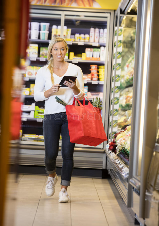Retrato da mulher que usa a tabuleta de Digitas ao andar em Supermar imagem de stock royalty free