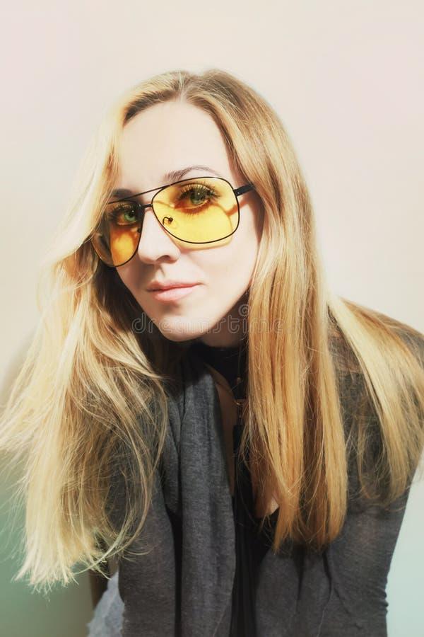 Retrato da mulher que veste óculos de sol amarelos fotografia de stock royalty free