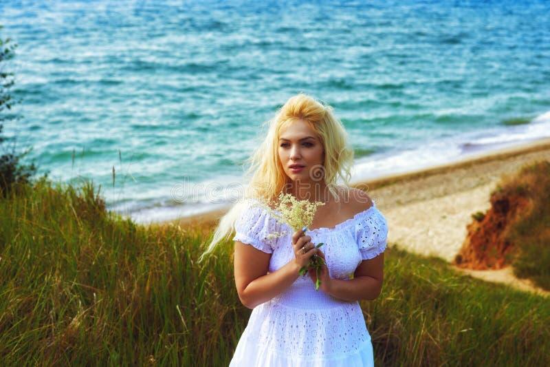 Retrato da mulher romântica nova no vestido branco no fundo do mar fotografia de stock