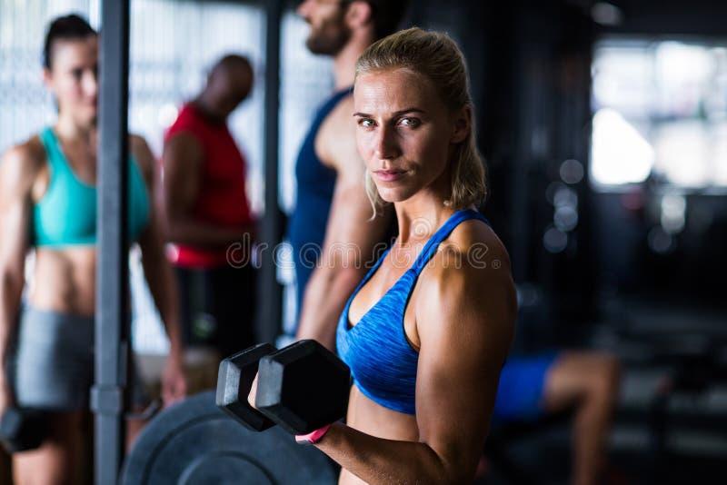Retrato da mulher séria que guarda o peso no gym foto de stock