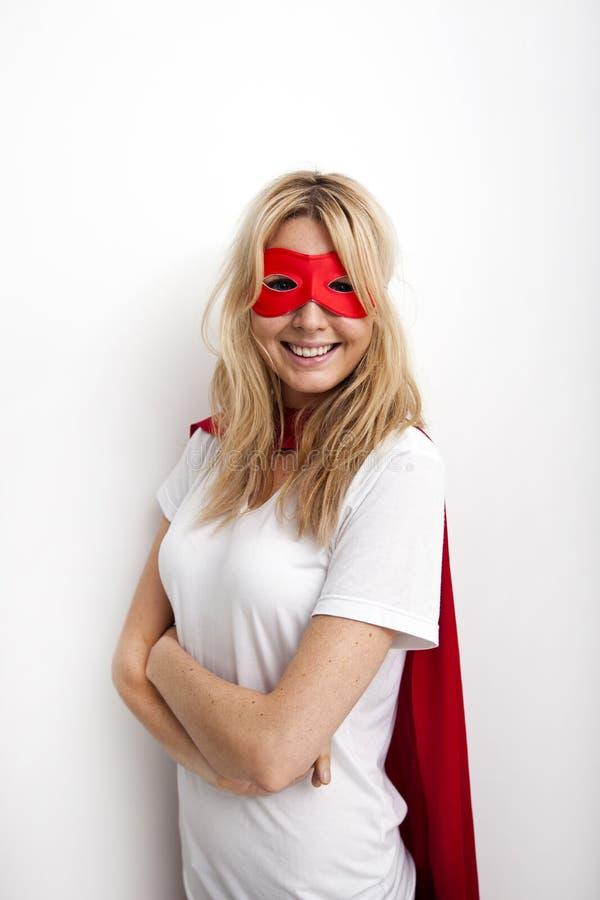 Retrato da mulher segura no traje do super-herói contra o fundo branco imagem de stock