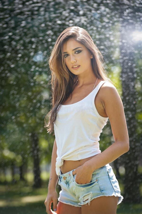 Retrato da mulher 'sexy' no pulverizador da água com a camisa branca de T Tem uma boa pele delicada, postura sensual, e sorri imagens de stock royalty free