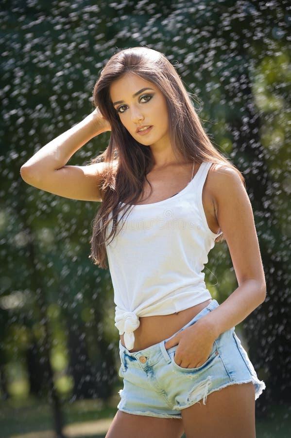 Retrato da mulher 'sexy' no pulverizador da água com a camisa branca de T Tem uma boa pele delicada, postura sensual, e sorri imagens de stock