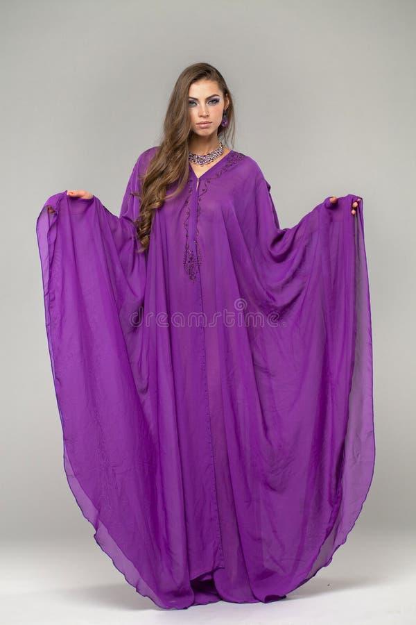 Retrato da mulher 'sexy' nova no árabe roxo da túnica imagens de stock royalty free