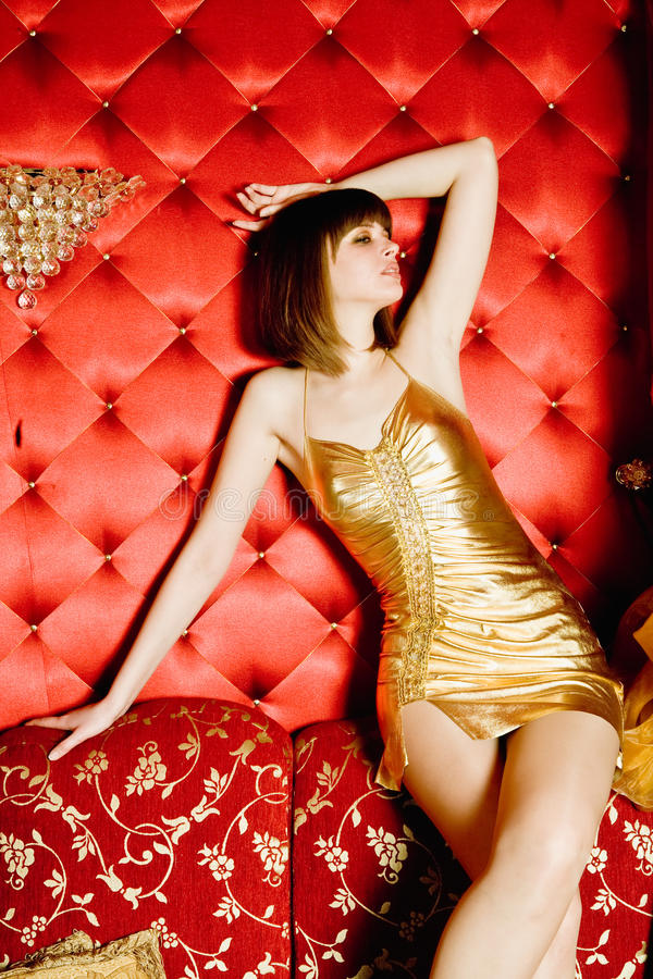 Retrato da mulher 'sexy' que senta-se no sofá imagem de stock