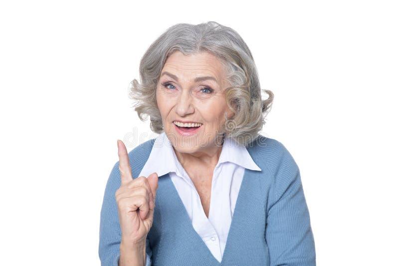 Retrato da mulher superior bonita que aponta para cima com dedo fotos de stock