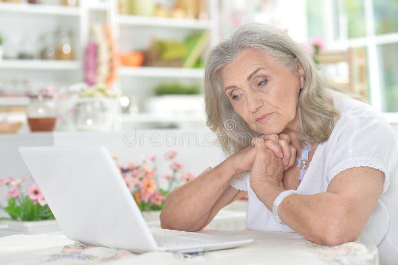 Retrato da mulher superior cansado que usa o portátil imagens de stock