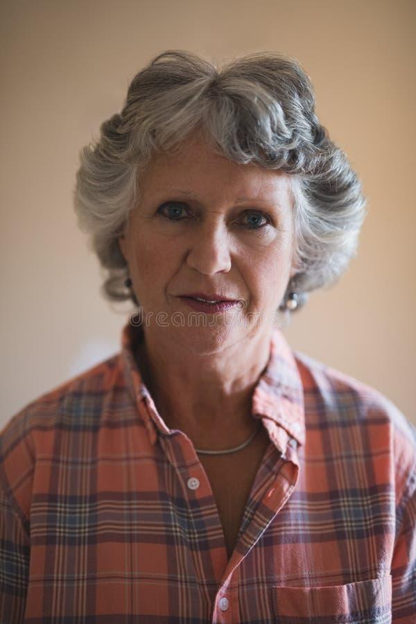 Retrato da mulher superior contra a parede em casa imagem de stock royalty free