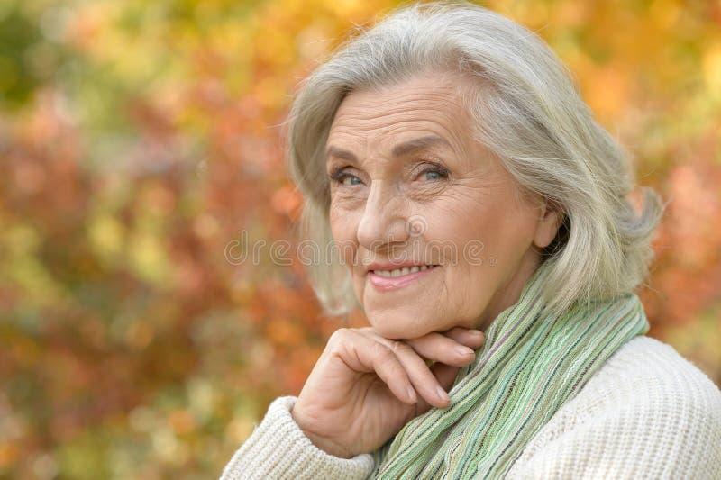 Retrato da mulher superior de sorriso agradável que levanta no fundo outonal borrado fotografia de stock