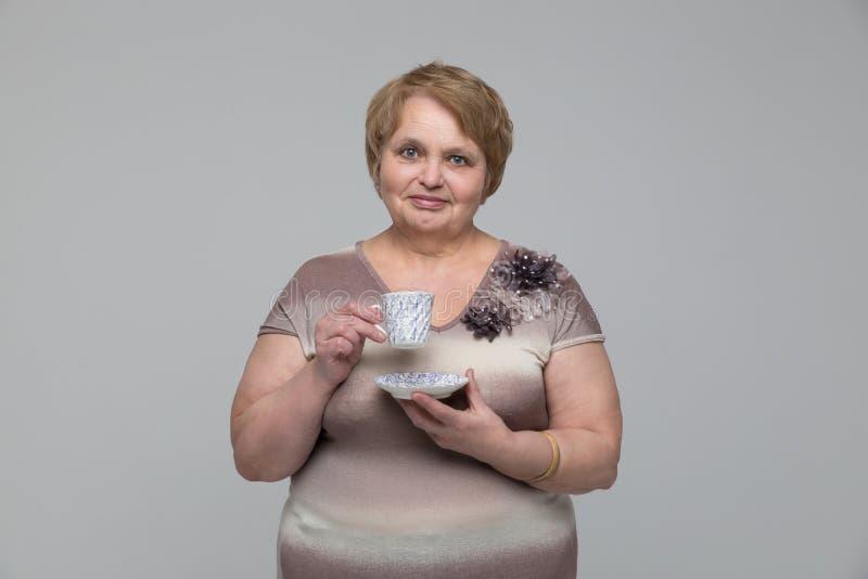 Retrato da mulher superior de sorriso com o copo do chá foto de stock
