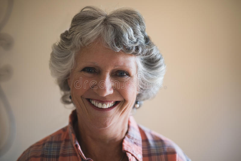 Retrato da mulher superior de sorriso contra a parede em casa imagens de stock