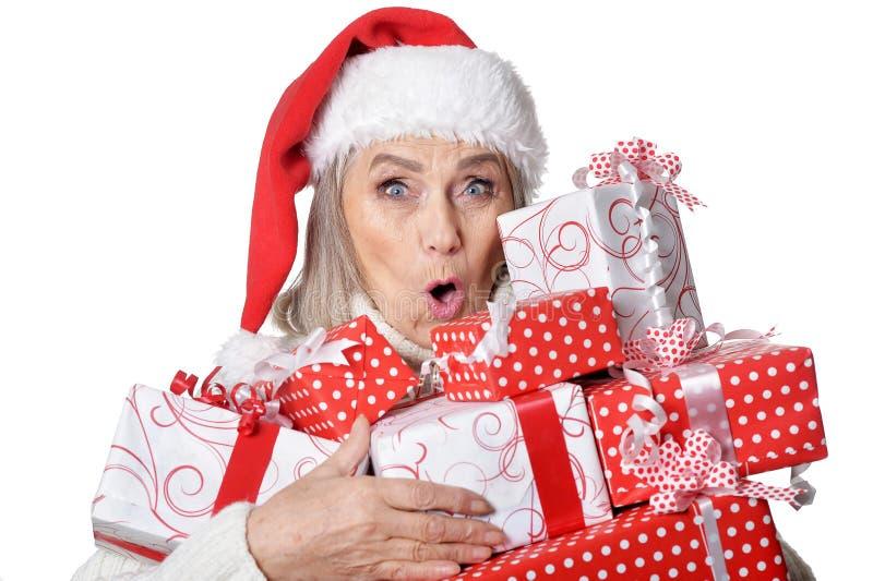 Retrato da mulher superior de sorriso no chapéu de Santa que levanta com presentes no fundo branco imagem de stock