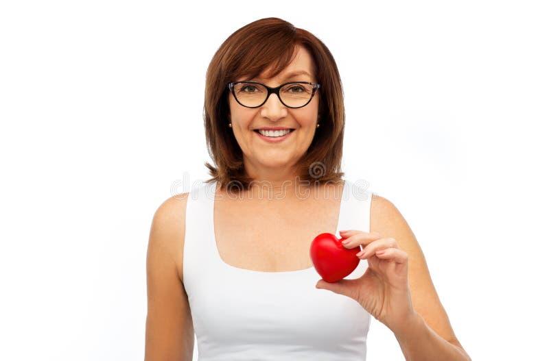 Retrato da mulher superior de sorriso que guarda o coração vermelho fotografia de stock royalty free