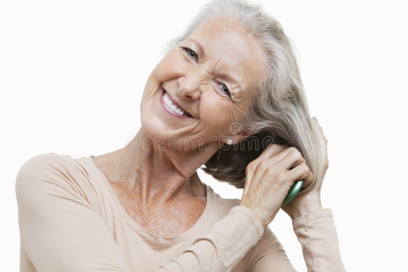 Retrato da mulher superior de sorriso que penteia seu cabelo contra o fundo branco imagem de stock royalty free