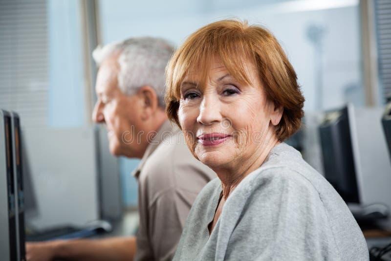 Retrato da mulher superior feliz na classe do computador fotografia de stock