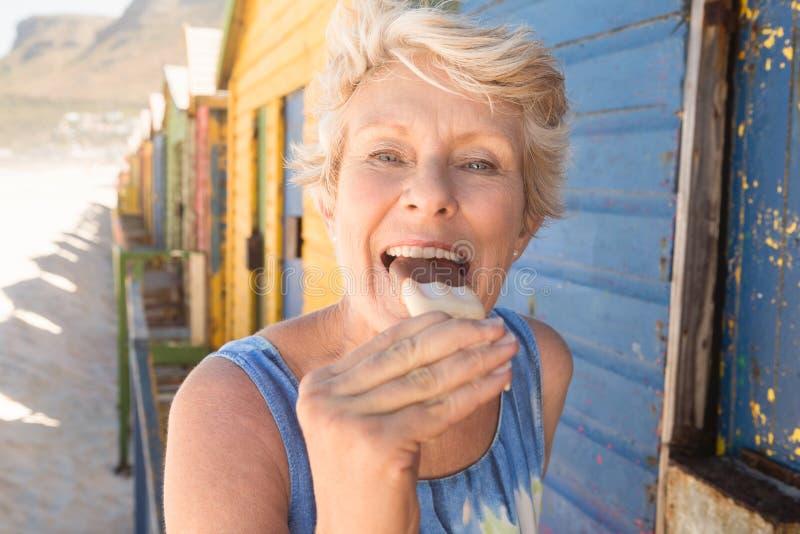 Retrato da mulher superior feliz que come o gelado ao estar pela cabana foto de stock royalty free