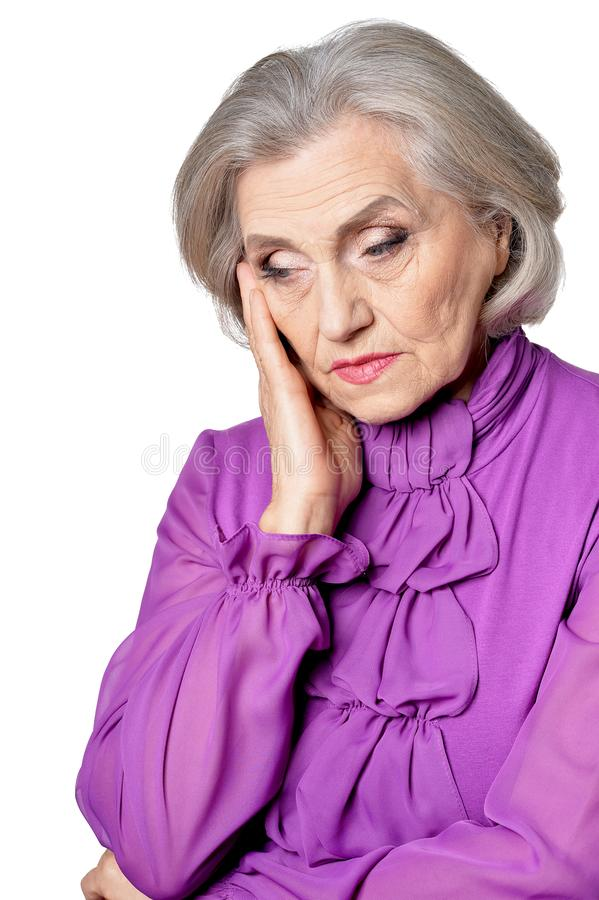 Retrato da mulher superior pensativa com dor de cabeça no fundo branco imagem de stock