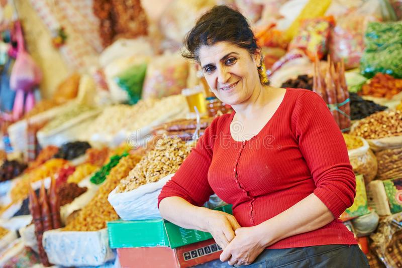 Retrato da mulher superior perto da especiaria, das porcas e do outro alimento no mercado oriental imagem de stock