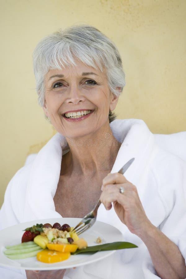 Retrato da mulher superior que come o alimento saudável imagem de stock
