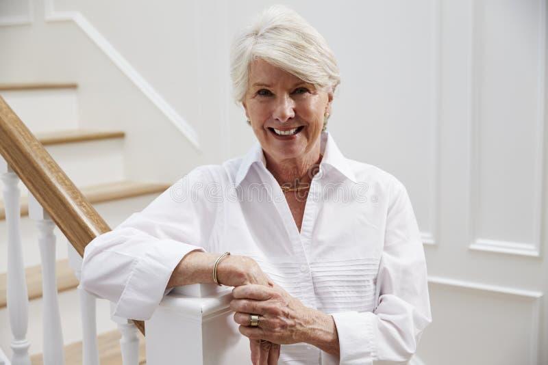 Retrato da mulher superior que está pela escadaria em casa fotos de stock