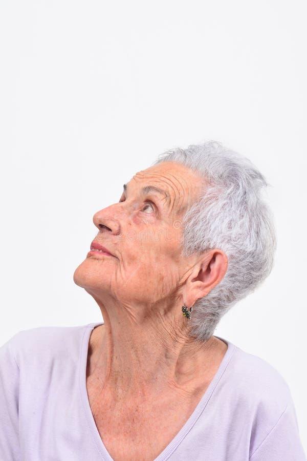 Retrato da mulher superior que olha acima no fundo branco imagem de stock royalty free