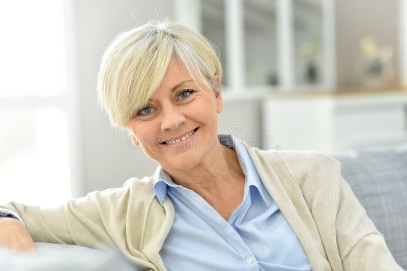 Retrato da mulher superior que sorri e que relaxa no sofá imagem de stock