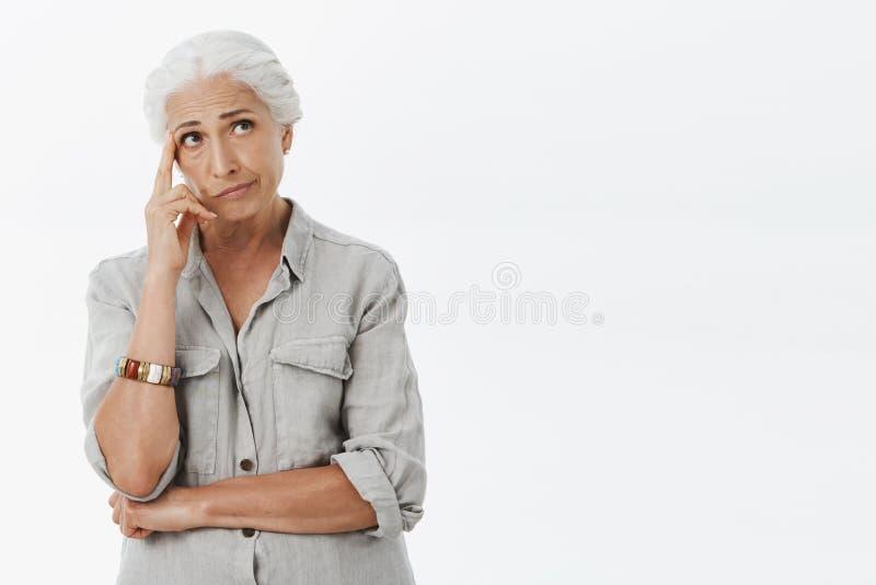 Retrato da mulher superior sombrio incomodada e interessada com cabelo branco que smirking guardando o dedo no templo e olhando imagem de stock