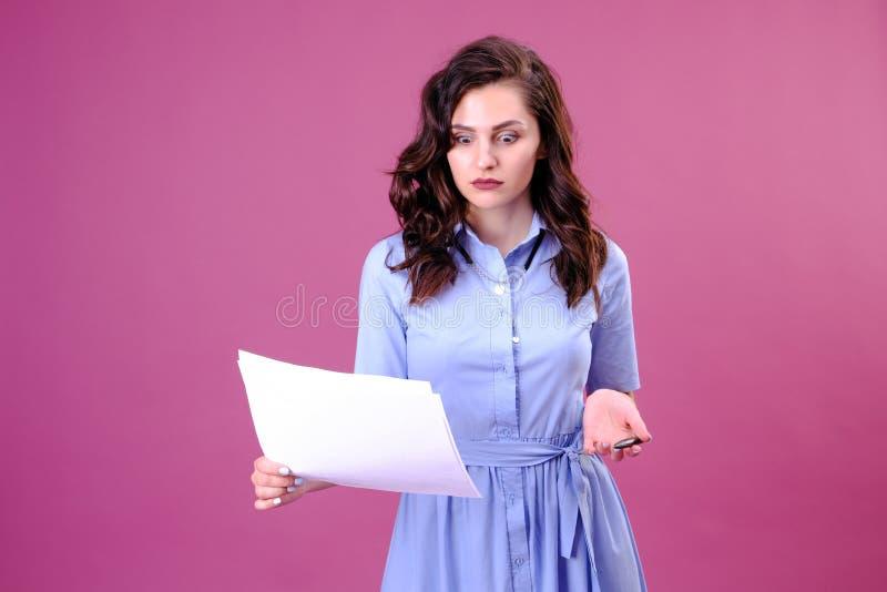 Retrato da mulher surpreendida com pena e papel Mulher de neg?cios no vestido azul na moda que guarda o papel e a pena beleza, fo fotografia de stock