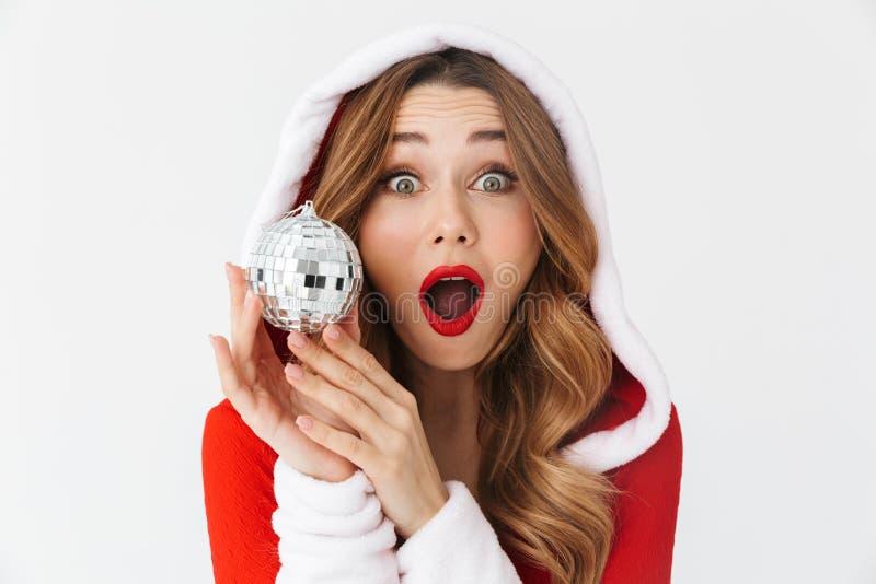 Retrato da mulher surpreendida 20s que veste o traje vermelho de Santa Claus que sorri e que guarda a bola da árvore de Natal, is fotos de stock