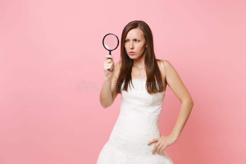 Retrato da mulher suspeito da noiva no vestido de casamento branco que examina a vista através da lupa sobre imagens de stock