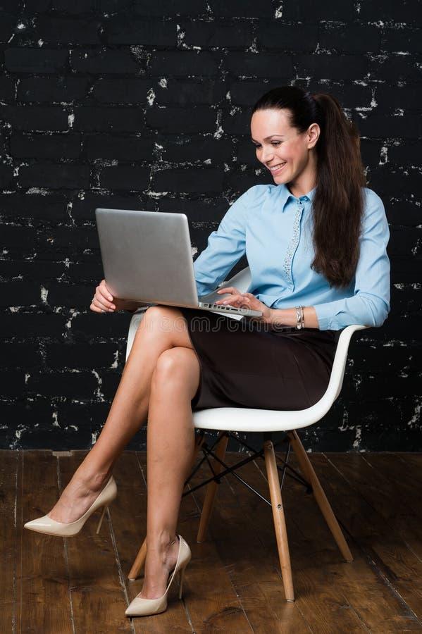 Retrato da mulher triguenha vestida elegante que senta-se no apartamento do sótão e que trabalha no portátil portátil fotos de stock