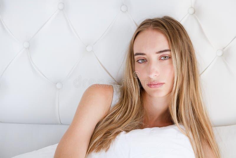 Retrato da mulher triste do yound que encontra-se na cama na sala clara, perda de apetite imagens de stock royalty free
