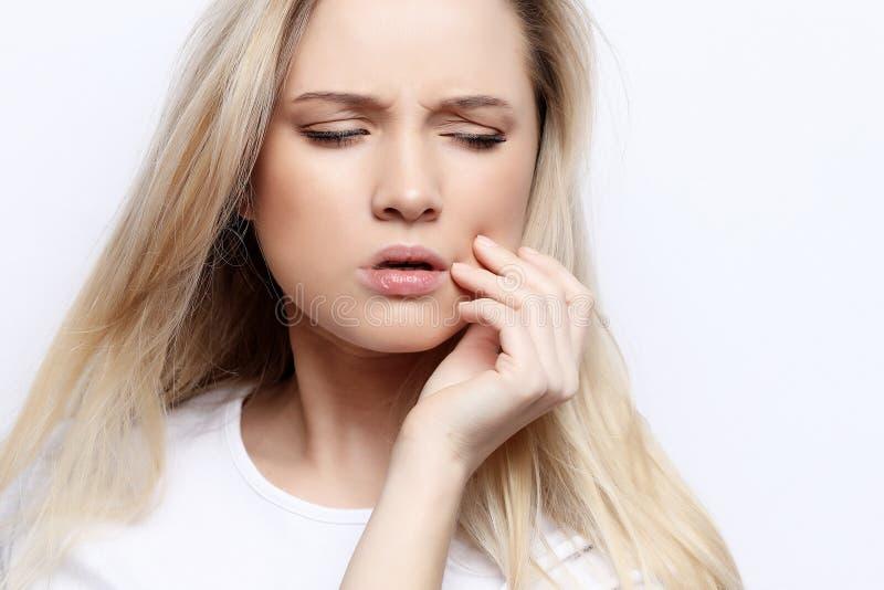 Retrato da mulher triste que tem a dor de dente e mordente tocante imagem de stock