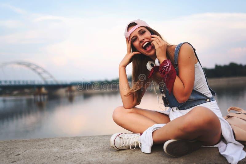 Retrato da mulher urbana nova de sorriso que usa o telefone esperto fora fotografia de stock