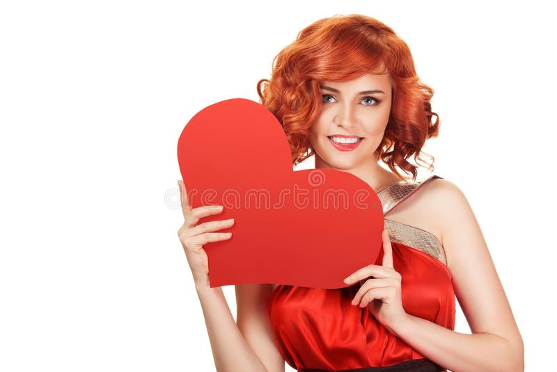 Retrato da mulher vermelha de sorriso do cabelo que guarda o coração vermelho grande foto de stock