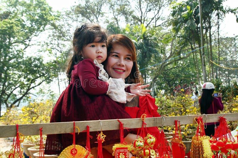 Retrato da mulher vietnamiana e da sua filha no vestido vermelho com as decorações vietnamianas tradicionais do ano novo na rua d foto de stock