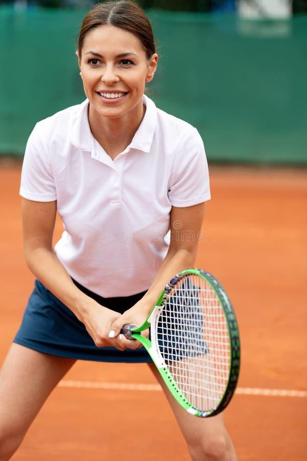 Retrato da mulher vigorosa que joga o tênis no campo de tênis exterior imagens de stock