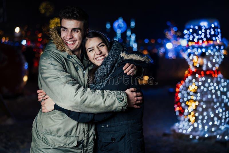 Retrato da noite de um par feliz que sorri apreciando aoutdoors do inverno e da neve Alegria do inverno Emoções positivas felicid fotos de stock