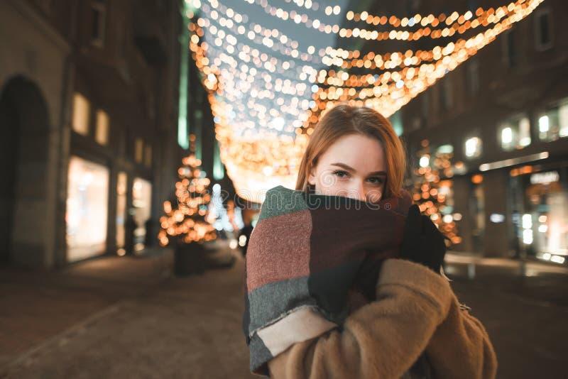 Retrato da noite de uma menina morna bonito da roupa no fundo da cidade e nas luzes do cenário fotografia de stock royalty free