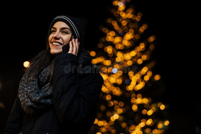 Retrato da noite de uma mulher moreno bonita que usa o smartphone durante o inverno frio no parque Alegria do inverno Feriados de fotos de stock royalty free